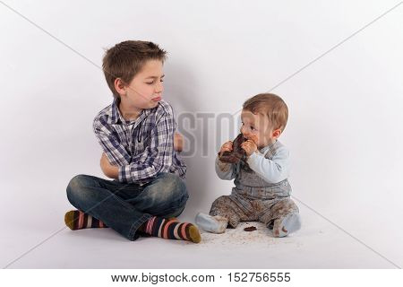 Siblings conflict and favoritism concept - Baby eating a plate of chocolate white his brother looks at him with folded arms jealousy