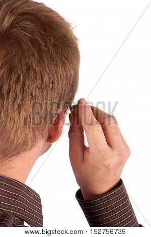 Deaf man's head and hand putting on his behind-the-ear hearing aid. Isolated on white.