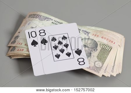 Playing Cards and Indian Currency Rupee bank notes on gray background