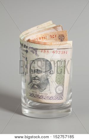 Money Indian Currency Rupee Notes in a glass on gray background