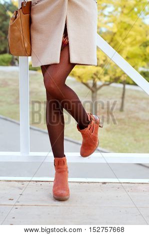 Woman wearing black tights and suede orange boots dressed in beige coat and mini skirt. Fall fashion;