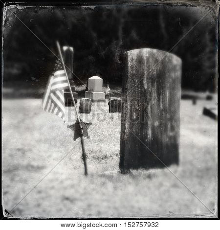 vintage tin type filtered black and white image of a cemetery grave head stone