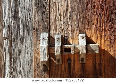 primitive wooden door latch against weathered wood