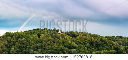 Vilnius, Lithuania. The Panoramic View Of The Famous White Monument Three Crosses On The Bleak Hill, Overgrown With Lush Green Vegetation In Summer, Blue Sky With Rainbow Background.