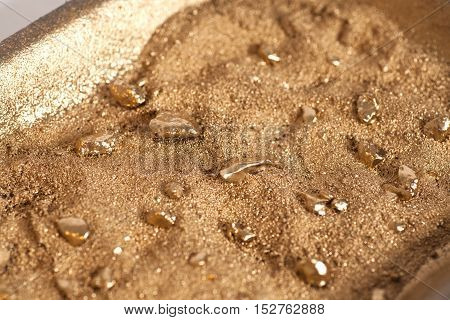Golden nuggets on grungy wash pan with sand