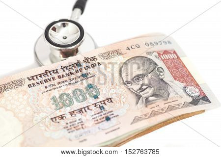 Stethoscope and indian 1000 rupee notes isolated