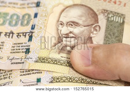 Hand with Indian one thousand rupee notes