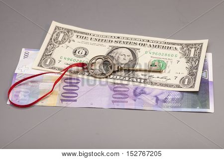 Key To Success With Red Bow on One American dollars and 1000 Swiss franc currency on gray