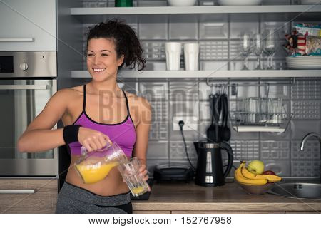 Portrait of a woman sipping orange juice in the kitchen.