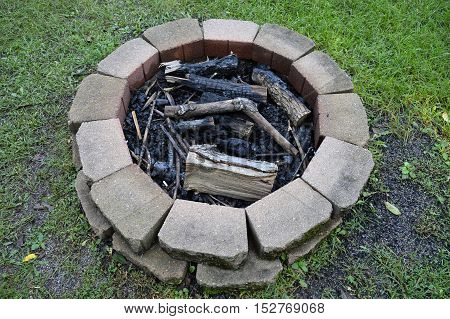Burned logs and ash in a fire pit