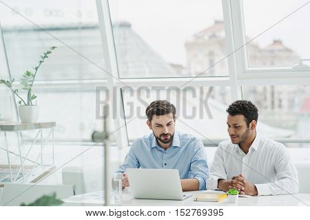Cheerful young men are working together in office. They are looking at the laptop with interest. The colleagues are sitting at desk