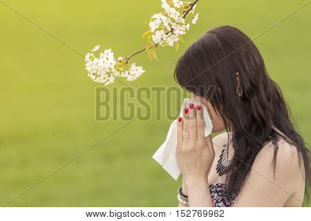 Beautiful hayfever girl wiping her nose in spring nature season. The beautiful young woman is pained by her allergy every year. She holds a tissue in her hands.