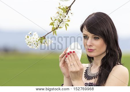 Unwell hayfever girl is pained in green spring nature season. The beautiful young woman is pained by her allergy every year. She holds a tissue in her hands.