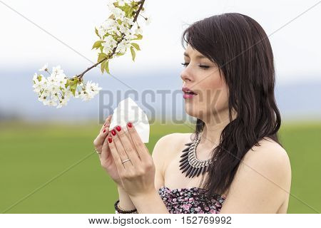 Sneezing hayfever girl is pained in green spring nature season. The beautiful young woman is pained by her allergy every year. She holds a tissue in her hands.