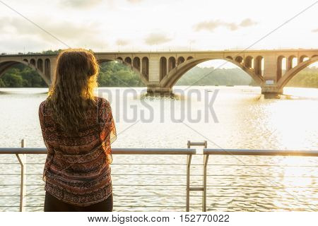 Back of young woman looking over potomac river with Francis Scott Key Bridge during sunset