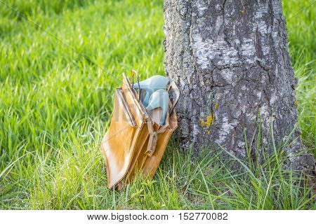 Business shoes pumps in bag wayside in nature arouse wanderlust. The scene symbolizes the passion for adventures and spontaneity and the desire for silence and resting.