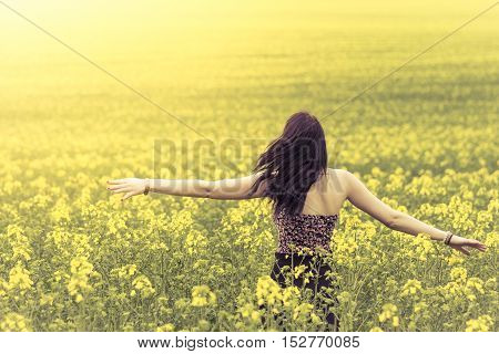 Beautiful genuine woman in sunny summer meadow from behind right. Attractive authentic young girl enjoying the warm summer sun in a wide green and yellow meadow. Part of series.