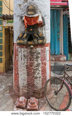 Madurai India - October 22 2013: Ten pillars of the Nayak palace remain in downtown. On one a colorful image of shivalingam has been chiseled. Bike and shop doors in photo too.