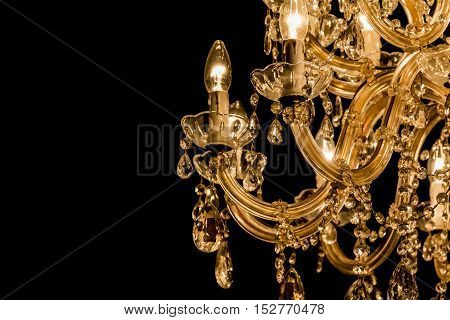 Gallant chandelier with light candles and dark side background. Luxury candelabra hanging on ceiling with lots of little gems. Black background and copyspace on the left side.