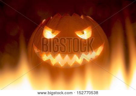 Bad carved halloween pumpkin in hot burning hell fire flames. The big helloween pumpkin has a mad face with glowing eyes and also a glow in its mouth and teeth. Perspective from bottom up.