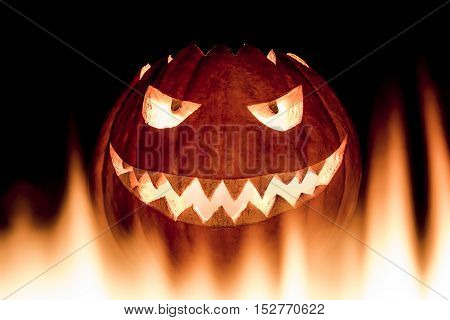 Scary carved halloween pumpkin in hot burning hell fire flames. The big helloween pumpkin has a mad face with glowing eyes and also a glow in its mouth and teeth. Perspective from bottom up.