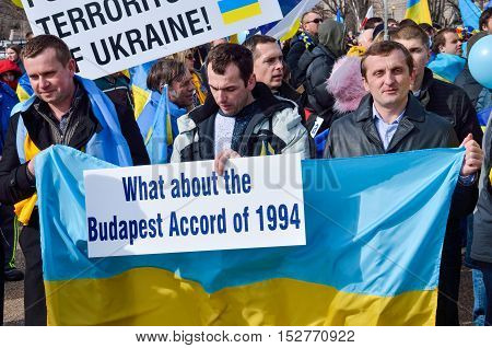 Washington DC, USA - March 6, 2014: Men holding Ukrainian flag with signs during protest by White House