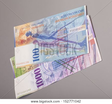 Swiss 1000 and 100 Franc notes isolated on gray