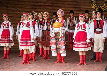 Silver Spring, USA - September 17, 2016: Girls and boys dressed in traditional red Ukrainian embroidered costume clothes dancing Hopak with bread at festival on stage