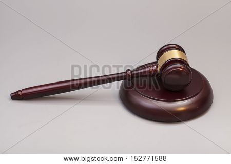 wooden judge gavel and soundboard on grey background