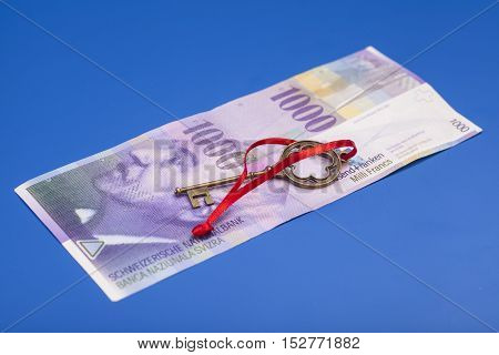 Key To Success With Red Bow on Swiss 1000 Franc note isolated on blue