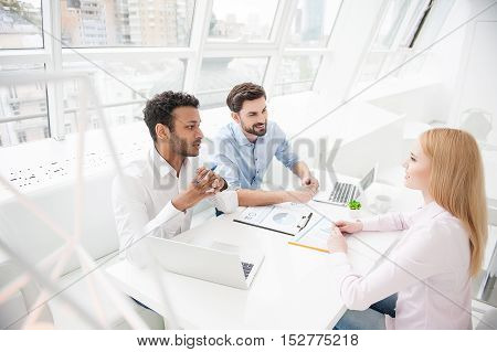 Putting their ideas on table. Top view of group of colleagues going over paperwork together in modern office