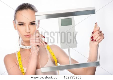 Confident slim woman is showing scales with proud. She is standing and carrying tape-line. Lady is looking forward seriously. Isolated