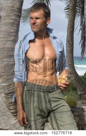Handsome scruffy Caucasian man with fit muscular torso wearing open button down shirt holding coconut under palm tree on tropical island beach