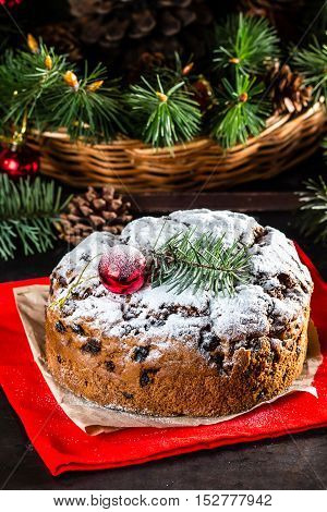 Christmas composition. Christmas cake - pan de pasqua - and Christmas New Year decoration - fir brunches, fir and pine cones, New Year balls, red napkin on black background