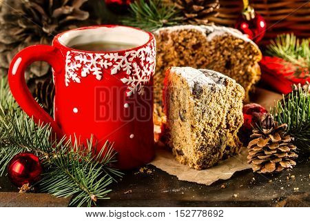 Christmas composition. Slice of Christmas cake pan de pasqua, red mug of tea and Christmas New Year decoration - fir brunches, fir and pine cones, New Year balls, red napkin on black background