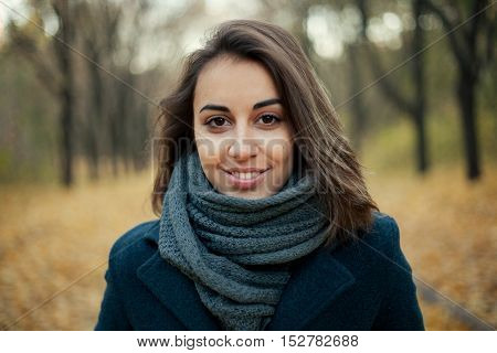 Autumn fashion girl wearing trench coat in sun flare foliage. Fall woman portrait of happy lovely and beautiful mixed race Caucasian young woman in forest in fall colors.