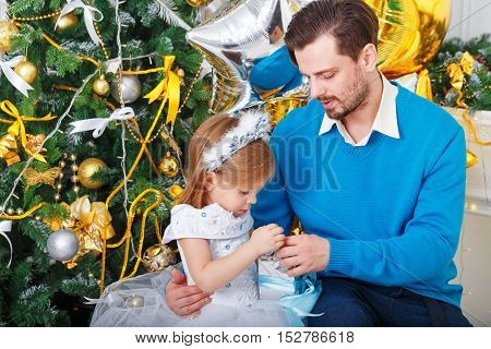 Father and daughter with gifts near a Christmas tree. Father hugging daughter and little cute girl unties the bow on the gift. Close-up. The festive mood. Family celebration.