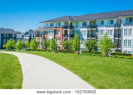 Concrete pathway across green lawn in front of residential condo building. Residential apartment building on sunny day with blue sky.
