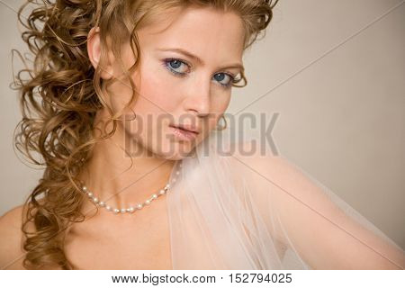 Horizontal close-up portret of bride with the veil on her shoulder