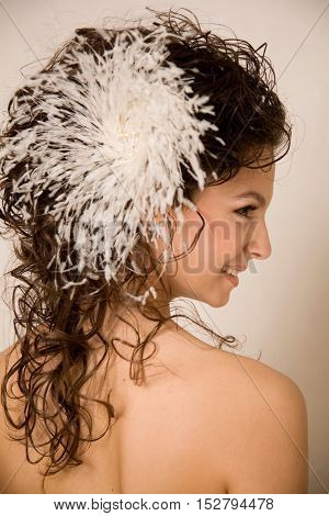Half face of the bride with the curly hair and feather hairpin in her hair