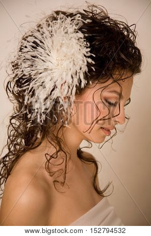 Profile of young beautiful bride with feather hairpin in her hair