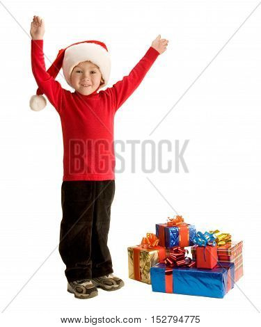 Little boy standing by the presents with raised arms; isolated on white background