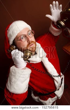 Thoughtful mandressed in Santa Clause costumeis talking on the retro phone.Braun background.