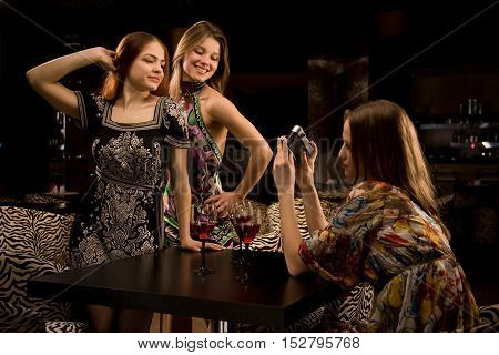 Three young woman in the nightclub are having fun and photografing each other