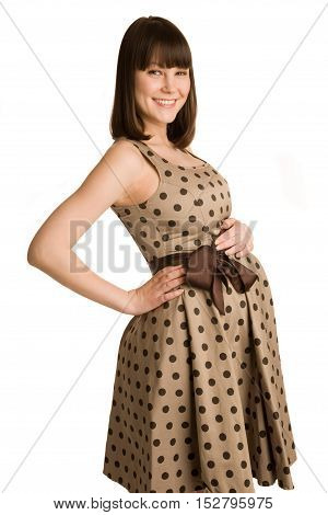 Cheerful pregnant woman in spotted dress.Isolated on the white background