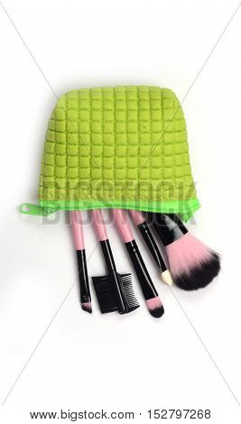 Cosmetics in green bag isolated over on white background.