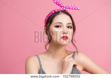 Portrait of beautiful pinup Asian woman with vintage makeup and hairstyle. Isolated on pink background