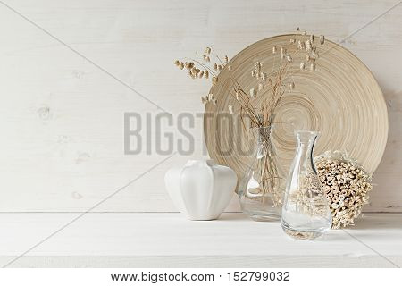 Soft home decor of glass vase with spikelets and wooden plate on white wood background. Interior.