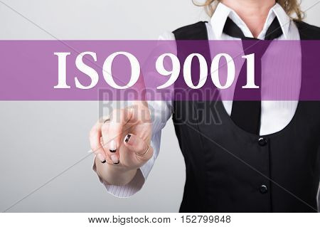ISO 9001 written on virtual screen. technology, internet and networking concept. woman in a black business shirt presses button on virtual screens.