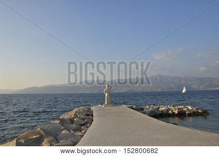 Pier with statue in Postira harbor with mountains in background picture from Brac Island in Croatia.
